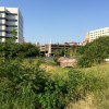 A view of the vacant lot that currently covers the Assunpink Creek, towards the obscured S. Broad Street Bridge. Across the street is Mill Hill Park.
