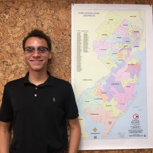 Miles Franklin standing next to map of New Jersey